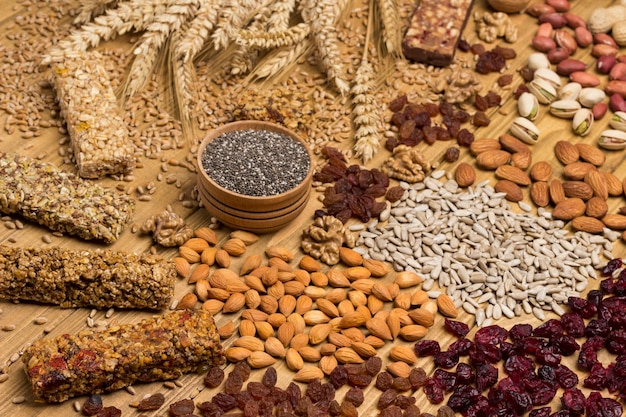 Balanced vegan snack, protein granola bar. nuts, seeds, cereals, black quinoa, spikelets of wheat. weight loss concept. top view. wooden surface. close up