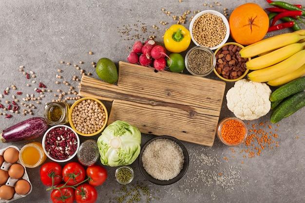 Сбалансированная вегетарианская диета органические продукты питания фон. еда для здорового питания, суперпродукты, вегетарианские варианты. овощи, фрукты, зелень, крупы
