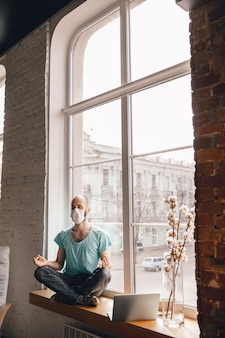 バランスのとれた検疫とフリーランスのオンライン作業中に自宅でヨガをしている若い男