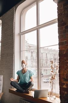 Equilibrato. giovane che fa yoga a casa mentre è in quarantena e lavora online come freelance