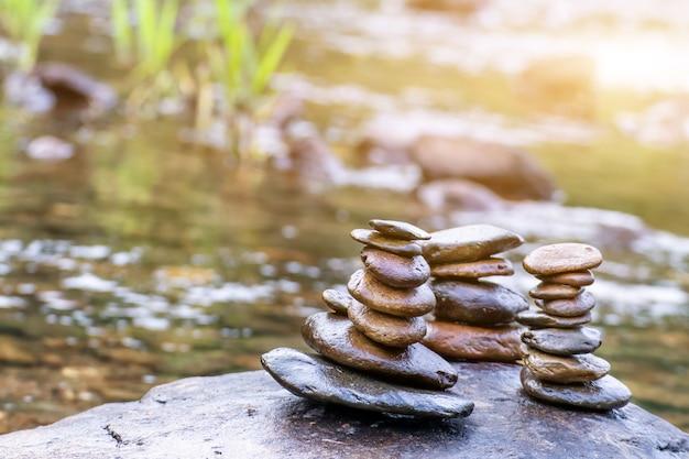 개울의 균형 잡힌 선 바위 스택, 바위에 쌓인 돌이있는 개울의 전망
