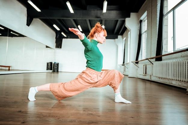 アサナのバランスを取ります。緑のタートルネックを身に着けてバランスの取れたアーサナをしている美しいスリムなヨガのコーチ