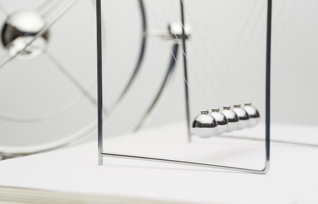 Балансирующие шары на белом фоне. бизнес-концепция. колыбель ньютона