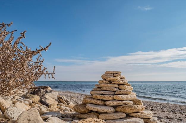 Balancing cairn pyramid on the shore