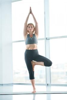 Balancing on one leg. woman on mat doing yoga next to a large window