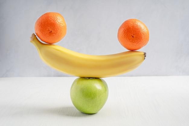 Уравновешивание сырого мандарина, спелого банана и зеленого кислого яблока на белом деревянном столе