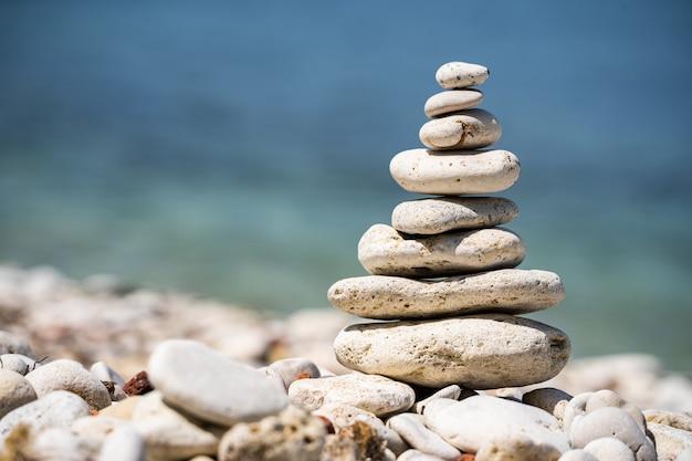 Балансирующая фигурка из гальки на берегу моря концепция медитации и умиротворения