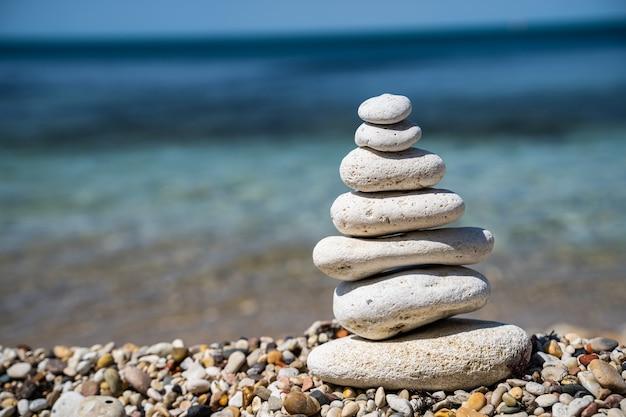 海の静けさと静けさの概念を背景に小石ピラミッドのバランスをとる Premium写真