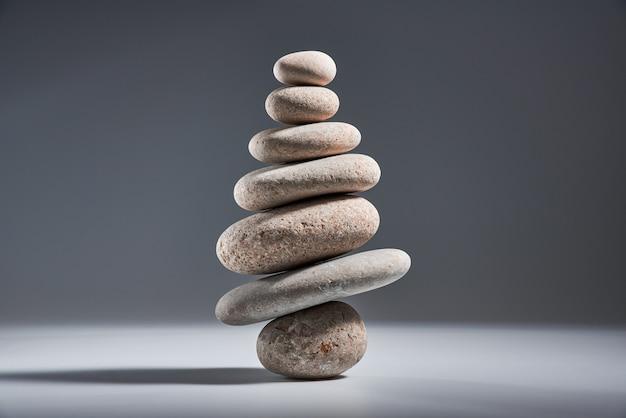 Балансирующая пирамида из морской гальки на сером фоне концепция гармонии и баланса