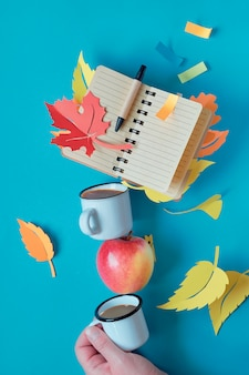 Balancing tower of coffee cups, autumn leaves and blank notebook