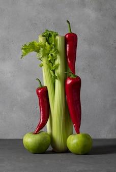 灰色のテーブルで野菜と果物のバランスをとる:セロリ、ピーマン、リンゴ。クリエイティブなコンセプト。垂直フォーマット