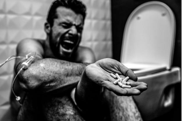 トイレの床で叫んで叫んでいる若い男のバルクと白の写真