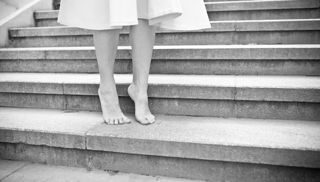 Balck and white young woman walking barefoot outdoors.