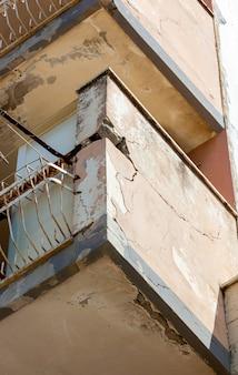 ひびの入ったコンクリートとさびた鉄のバルコニー。改修が必要です。