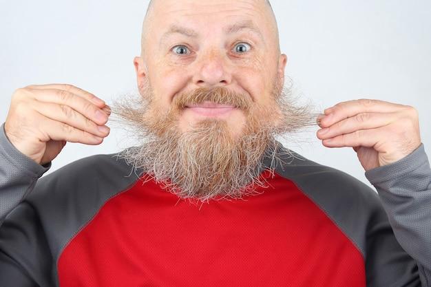 Лысый, бородатый, улыбающийся мужчина трогает бороду