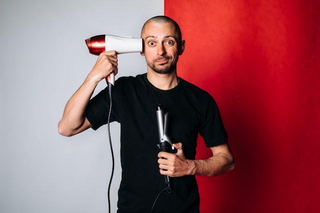 A bald brutal man, holding a hair dryer and curling tongs in his hand, dries his hair and baldness . a man in a black t-shirt on a red and gray background. space for text. hair care concept