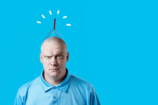 Bald brutal man scratching his head with a special device on blue