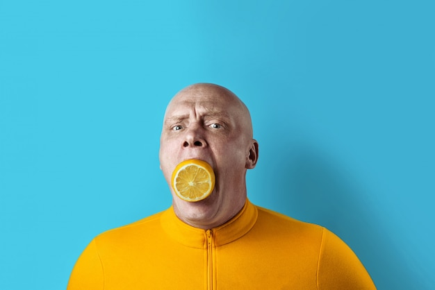 Bald brutal man with lemon in his mouth and yellow jacket on blue background