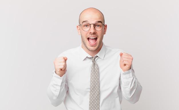 대머리 사업가는 충격을 받고 흥분되고 행복하며 웃고 성공을 축하하며 와우!