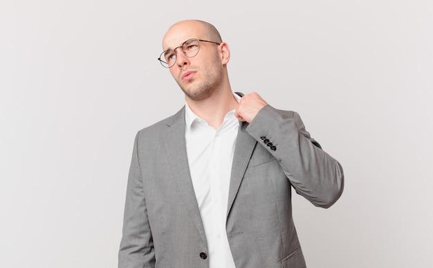 대머리 사업가는 스트레스를 받고, 불안하고, 피곤하고, 좌절하고, 셔츠 목을 당기고, 문제에 좌절하는 것처럼 보입니다.