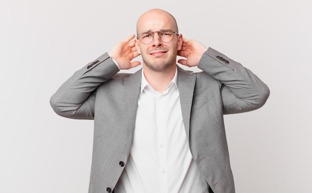 대머리 사업가는 스트레스, 걱정, 불안 또는 두려움을 느끼고 머리에 손을 얹고 실수로 당황합니다