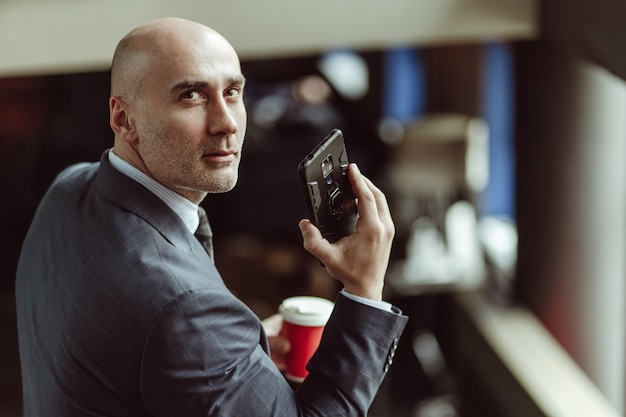 Bald businessman looking at camera turned from back. caucasian man wearing a business suit