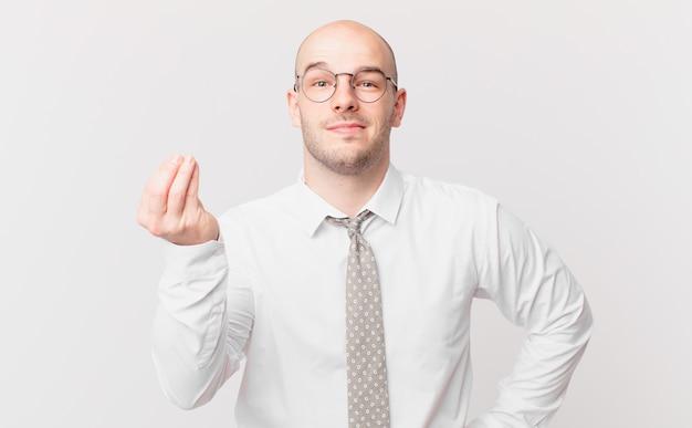 禿げたビジネスマンが、借金を返済するように言って、お金やお金のジェスチャーをします!
