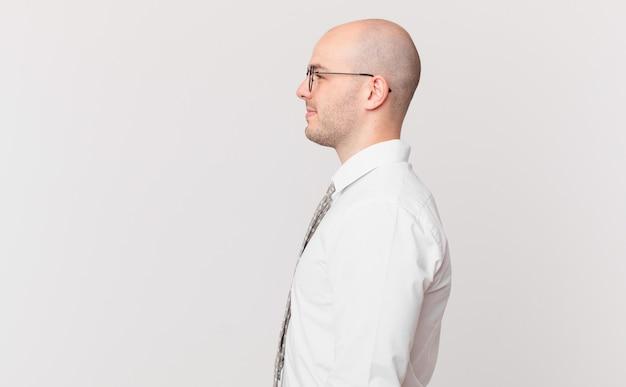 프로필 보기의 대머리 사업가는 앞서 공간을 복사하고, 생각하고, 상상하거나, 공상을 하려고 합니다.