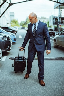 Bald businessman walking on the airport parking lot with suitcase and parked cars
