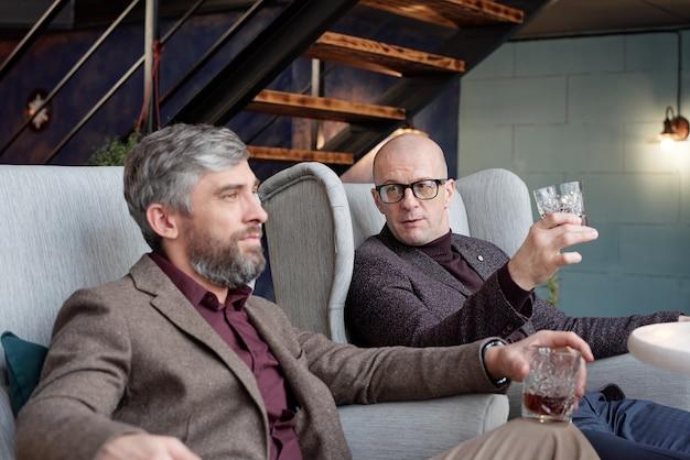 リビングルームに座って同僚と仕事について話し合うウイスキーグラスを持つはげたビジネスマン