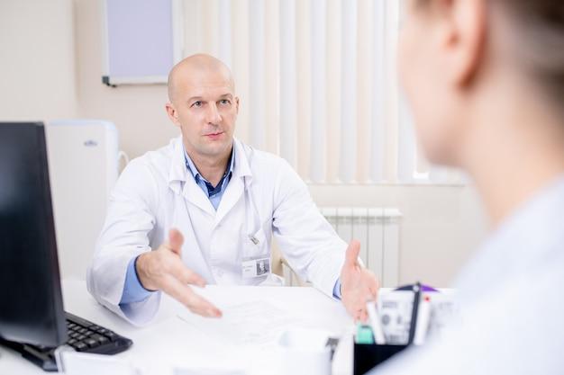 重要な情報を説明したり、推奨事項を提示したりしながら患者を見つめる自信のあるハゲ医師