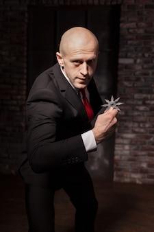 スーツと赤いネクタイの禿げた契約殺人者はアスタリスクの忍者を保持します。