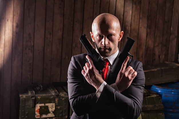 Bald contract killer in suit with two pistols.