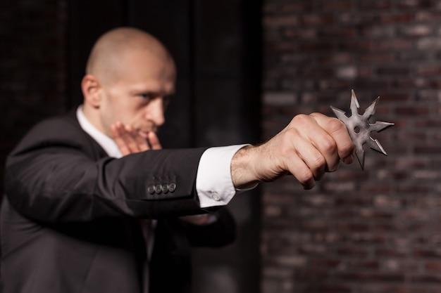スーツと赤いネクタイのハゲ契約殺人者はアスタリスク忍者を保持します。