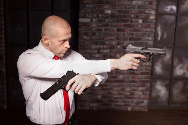 赤いネクタイでハゲを雇ったキラーはピストルを狙う