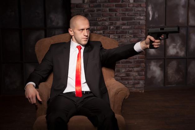 スーツと赤いネクタイのハゲキラーはピストルを目指しています