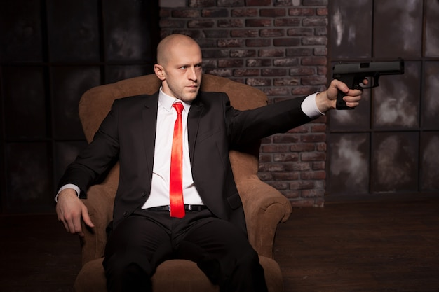 Bald killer in suit and red tie aims a pistol