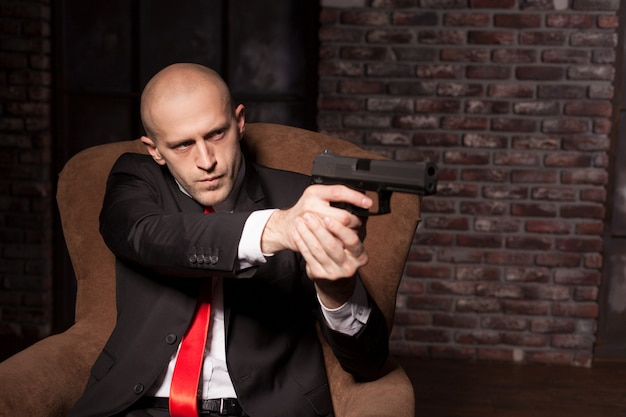 Bald killer in suit and red tie sitting in chair and aims a pistol.