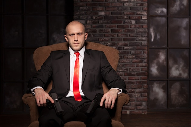 Bald killer in suit and red tie sitting in a chair and holding pistols in hands