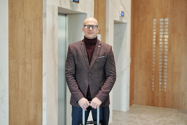 Bald male business traveler in suit and eyeglasses holding suitcase by handle while standing by elevator door