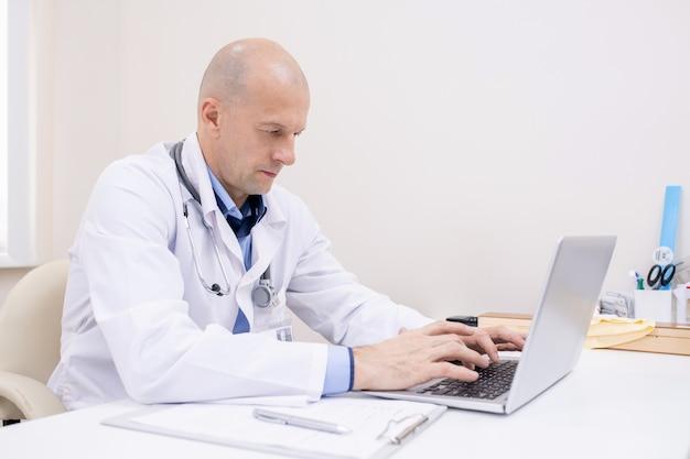 クリニックで医療データをネットでサーフィンしながらラップトップの前で仕事に集中する白衣のハゲの男性専門家