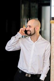 Лысый бизнесмен разговаривает по телефону