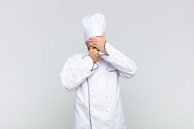 Лысый мужчина закрывает лицо обеими руками, говоря нет! отказ от фотографий или запрет на фотографии