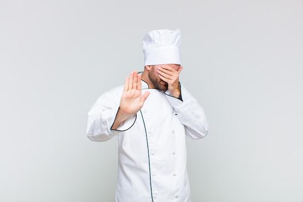 Лысый мужчина закрывает лицо рукой и поднимает другую руку вперед, чтобы остановить камеру, отказываясь от фотографий или изображений