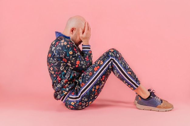 Bald man in fashionable clothes sitting with hands on his gace over pink background.