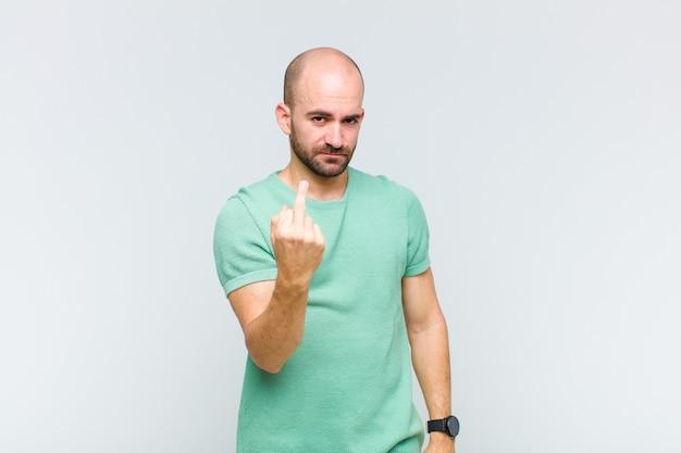 대머리 남자는 화가 나고, 짜증이 나고, 반항적이고 공격적이며, 가운데 손가락을 뒤집고, 반격