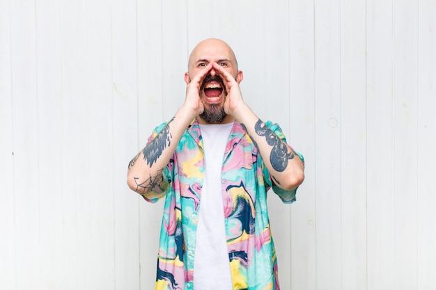 대머리 남자가 행복하고 흥분되고 긍정적 인 느낌, 입 옆에 손으로 큰 소리를 지르며 외침