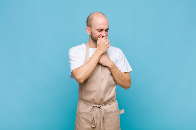 Bald man feeling ill with a sore throat and flu symptoms, coughing with mouth covered