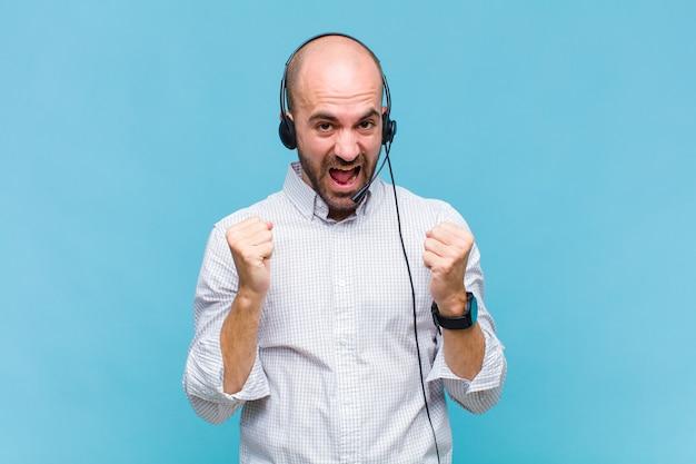 Лысый мужчина потрясен, взволнован и счастлив, смеется и празднует успех, говоря