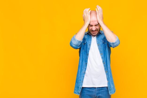대머리 남자는 스트레스와 불안, 우울, 두통으로 좌절감을 느끼며 양손을 머리로 들어 올립니다.